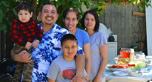 Salvador Jimenez and his family are smiling after they get solar installed by GRID Alternatives.